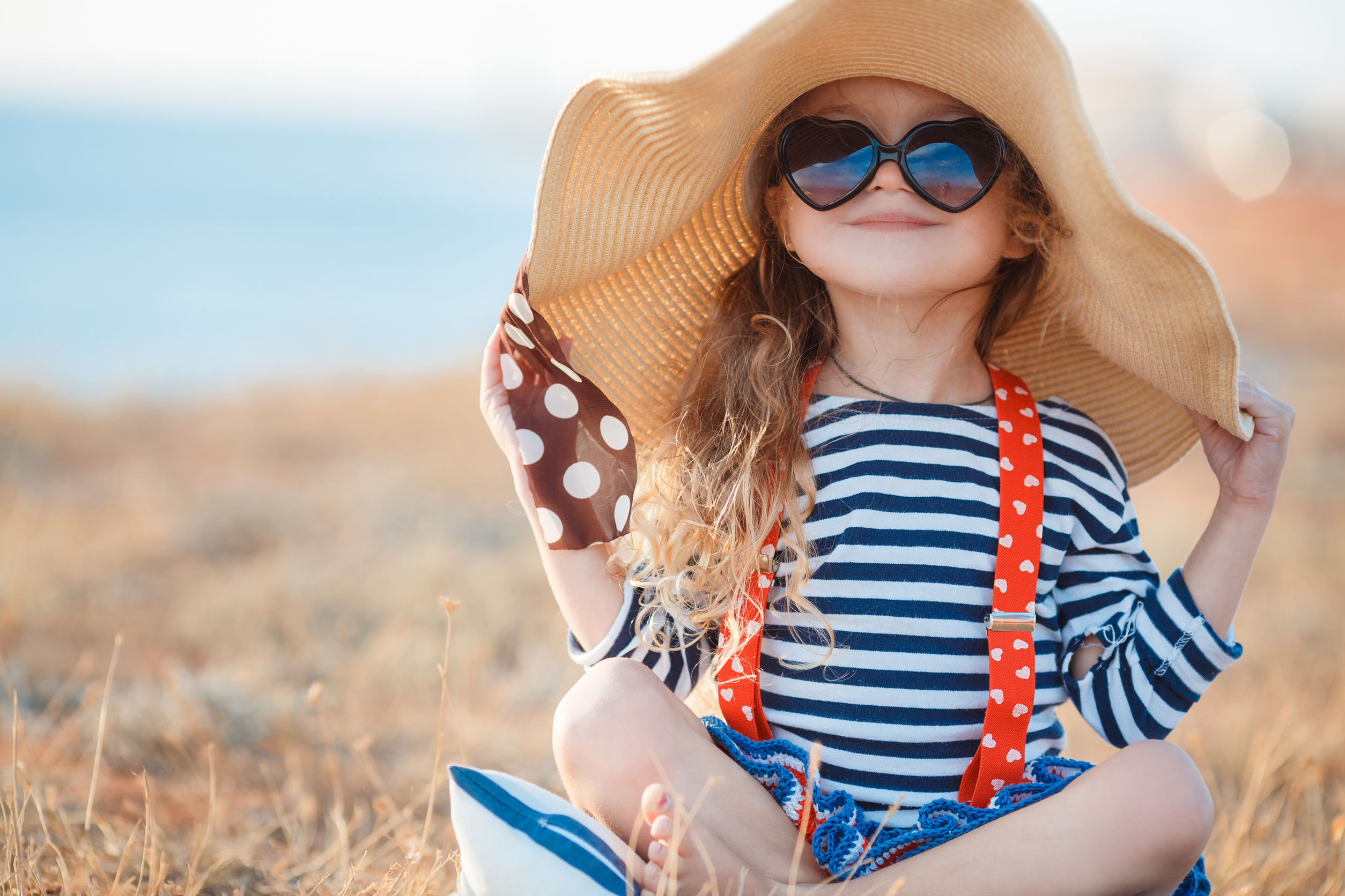45459344 - happy little girl in a large hat, beautiful young lady, a brunette with long curly hair, dressed in a striped sailor shirt and red suspenders, wearing dark sunglasses, sitting on a rocky beach in a big straw hat.